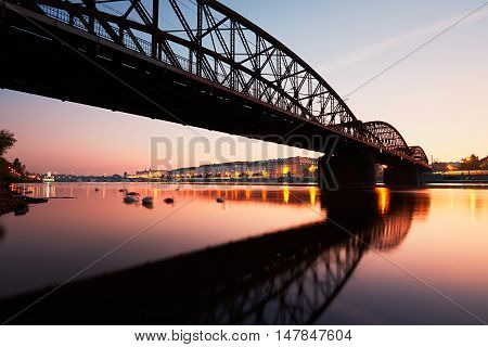 Amazing sunrise in the city. Railway bridge (with reflection in the river) and embankment in Prague Czech Republic.