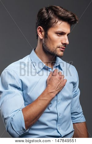 Close up portrait of a casual handsome man buttoning his shirt isolated on a gray background