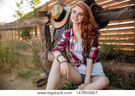 Cheerful pretty redhead young woman cowgirl sitting and smiling outdoors