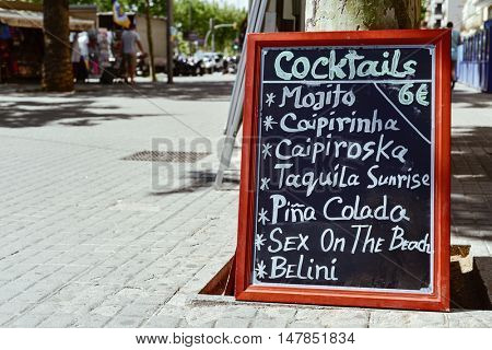 a menu chalkboard with a list of cocktails in front of a restaurant in a pedestrian street in Barcelona, Spain, with drinks like mojito caipirinha, caipiroska, pina colada or sex on the beach