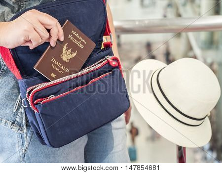 Single woman hold Thailand passport on her hand over blue shoulder bag