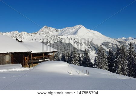 Wintery landscape in Gstaad Swiss Alps. View from Mt Hohe Wispile. Snow covered Mt Lauenenhorn. Traditional timber hut.