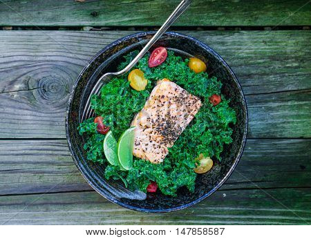Healthy kale salad with baked salmon and tomatoes on wood background. Toning.