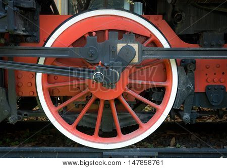 Red wheel detail of old steam train with black side rods