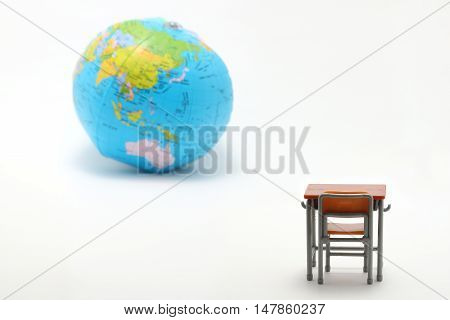 Miniature school study desk and globe on white background.