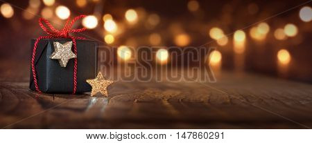 Festive shining Christmas background with a gift and bokeh