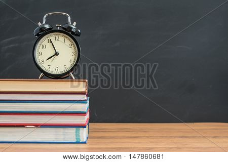 Alarm Clock And Book On Student Desk In Front Of Blackboard