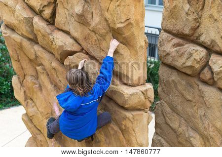 Boy climbing on the outdoor climbing wall
