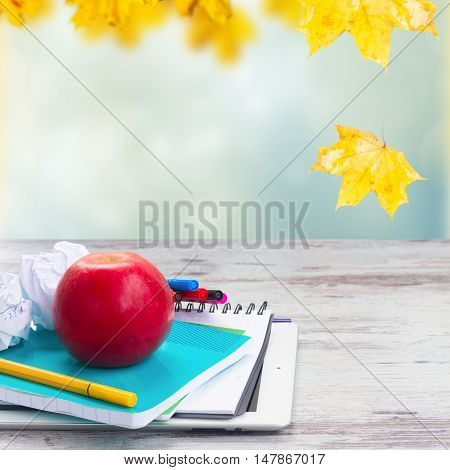 Apple with school supplies on white aged wooden table, fall garden in background