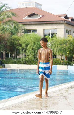 Boy walking along swimming pool. Hot summer day.