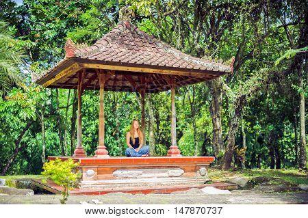 Girl Meditates In The Gazebo In The Garden Bali