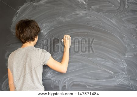 Boy with chalk in hand writting on empty blackboard