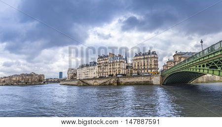 Seine River in Paris on a cloudy day - Panorama with the river Seine its bridges and the Parisian buildings on its shore. Picture taken in Paris France.