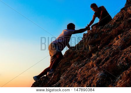 Man Rock Climbing with another Man Helping