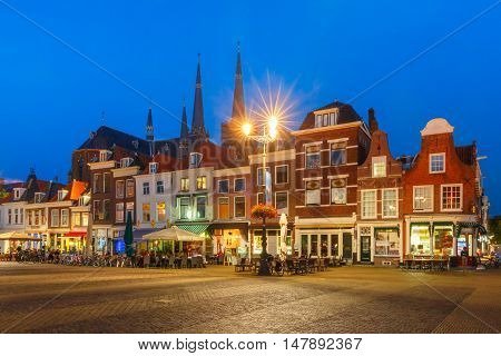 Typical Dutch houses on the Markt square in the center of the old city at night, and Maria van Jessekerk on the background, Delft, Holland, Netherlands
