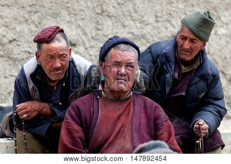 LAMAYURU, INDIA - JUNE 17, 2012: Three men praying in Lamayuru Gompa during Yuru Kabgyat festival