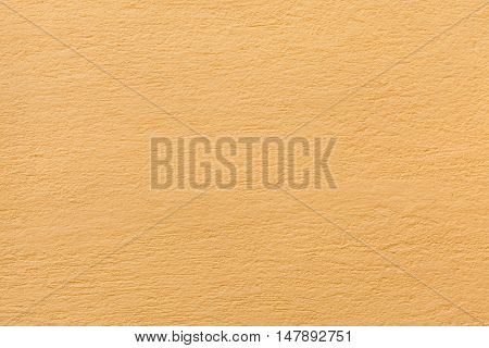 Yellow ochre painted stucco wall. Background texture.
