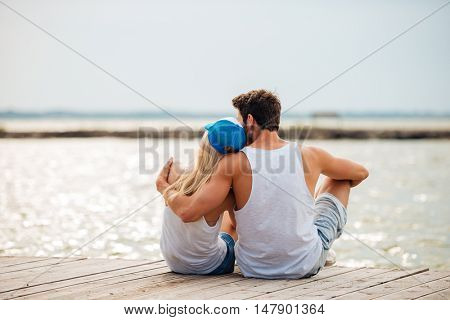 Loving couple on the beach hugging while sitting and looking at the sea