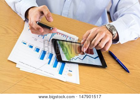 Close-up of a Businessman Analyzing Business Graphs on a Digital Tablet while Using Smartphone