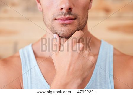 Closeup of pensive serious young man touching his chin over wooden background