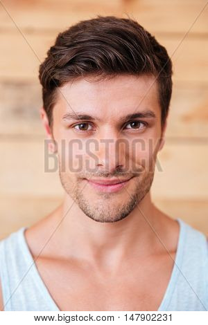 Closeup of smiling handsome young man over wooden background