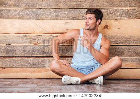 Happy attractive young man sitting with legs crossed and pointing away over wooden background