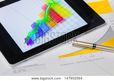 Digital Tablet and Documents with Business Graphs