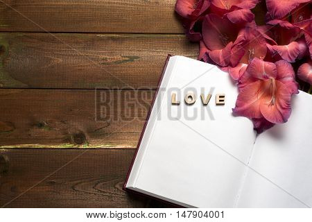 Open book on light table. The flower on a background of book. Back to school. Copy space