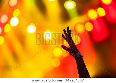 Raised Hands with Stage Lights on Background