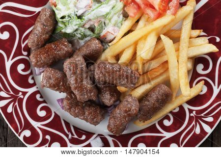 Cevapcici, bosnian minced meat kebab with salad and french fries