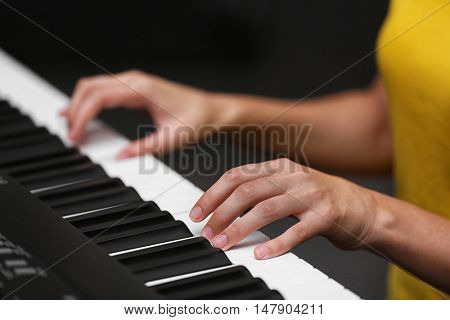 Female hands playing on synthesizer