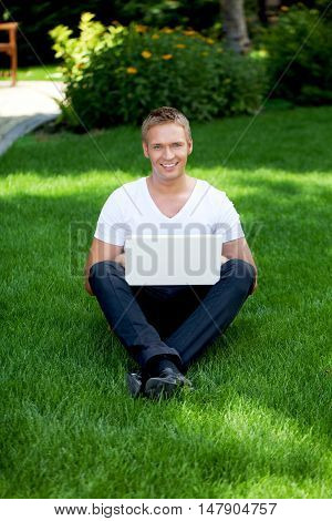 Man sitting in the grass using a laptop