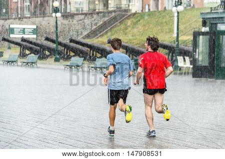 Quebec City, Canada - July 27, 2014: Two guys run in the heavy rain on a street close to Chateau Frontenac.
