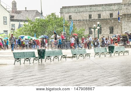 Quebec City, Canada - July 27, 2014: Crowd of people taking out umbrellas and walking in heavy rain on boardwalk street close to Chateau Frontenac.