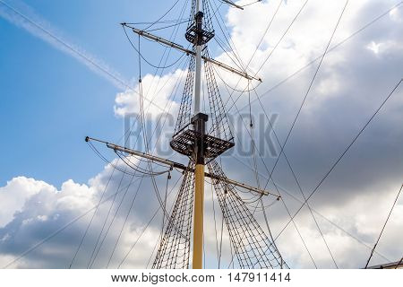 Ship's mast sailboat on background of clouds in the sky. The romance of travel and far wandering. Background marine themes. Ocean transport ship under sail.