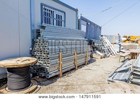Cable trays and cord spools are stacked among container office is placed at construction site waiting to be used in new edifice.