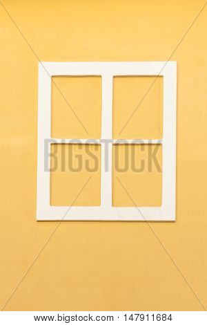 White window frame without glass in a yellow wall