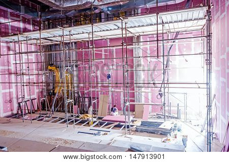 Empty scaffolding is placed against plasterboard wall at new theater with back light from outside.