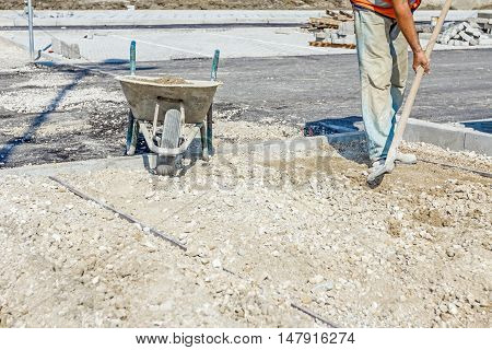 Worker is leveling gravel with shovel at new parking place by removing excess material.