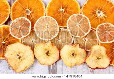 Slices Of Dried Lemon, Orange And Apple On Old Wooden Background