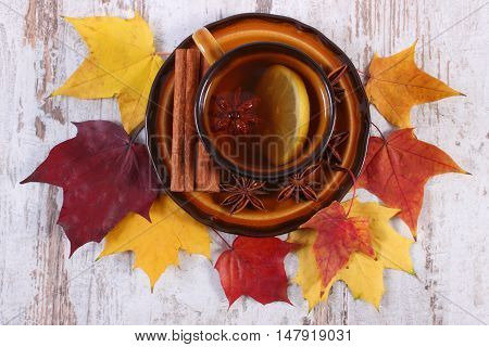 Cup Of Tea With Lemon, Spices And Autumnal Leaves On Wooden Background