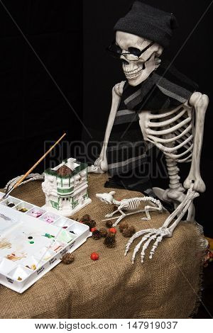 Halloween skeleton holding a brush and painting statuary and decorations for the celebration