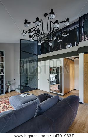 Light modern interior with light walls and parquet with red carpet on the floor. There is blue sofa with pillows, shelves, stair, glass wall, mirror, door. Higher there is cloakroom and chandelier.