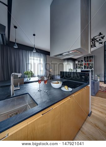 Modern kitchen with kitchen island with hood, table with chairs. Island have black tabletop, sink with tap, cooker, glasses and plates with pears. Blue sofa and bookshelves are on the background.