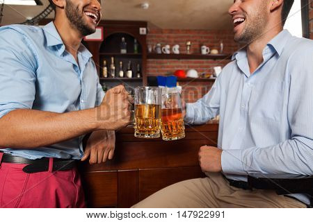 Two Man In Bar Clink Glasses Toasting Sit At Table, Drinking Beer Hold Mugs Close Up, Friends Wear Shirts Pub Communicate Talking