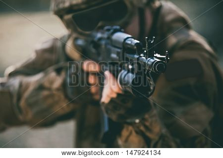 The soldier in the performance of tasks in camouflage protective gloves helmet and tinted glasses holding a machine gun takes aim for shot. War Zone.