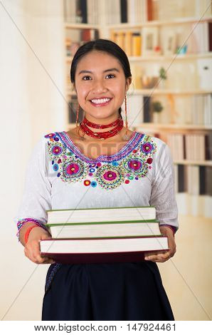 Beautiful young lawyer wearing traditional andean blouse and red necklace, holding stack of books, smiling to camera, bookshelves background.