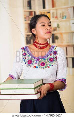 Beautiful young lawyer wearing traditional andean blouse and red necklace, holding stack of books, upset facial expression, bookshelves background.