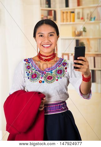 Beautiful young lawyer wearing traditional andean blouse and necklace, holding red jacket while using mobile phone, smiling happily, bookshelves background.