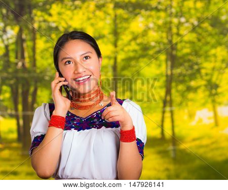 Beautiful young woman wearing traditional andean blouse with necklace, standing posing for camera, holding mobile phone talking, green forest background.